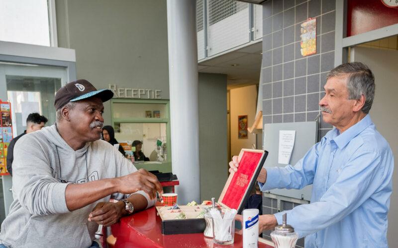 Buurtmedewerker biedt buurtbewoner een kopje koffie of thee aan in buurtontmoetingsplek.